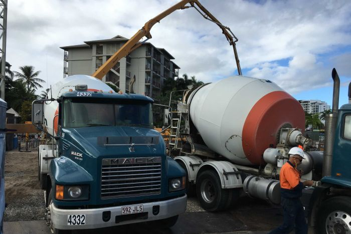 Two concrete trucks parked side-by-side wait their turn to pour concrete at the site of the Cairns Aquarium.