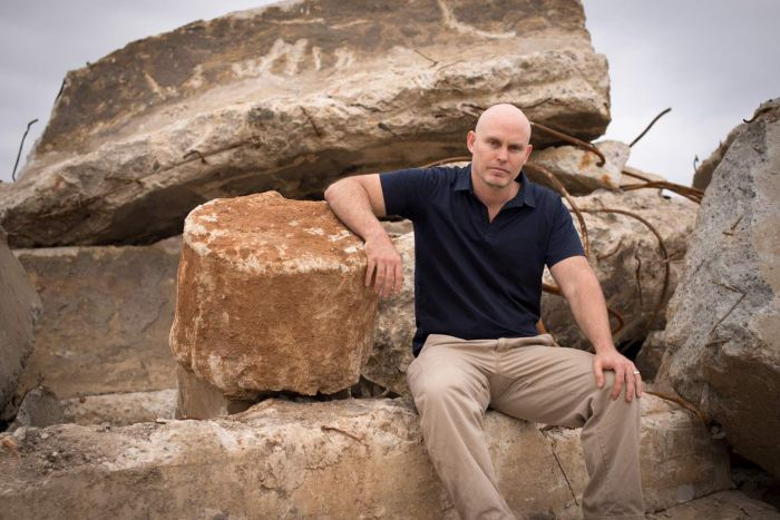 Dan Hannagan sits on top of large pieces of concrete recovered from demolition sites around Cairns.