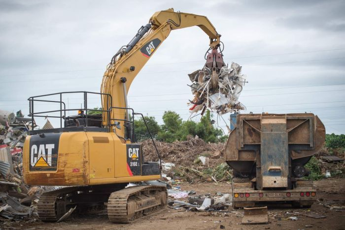 An excavator with a claw attachment loads light-gauge steel into a machine that will compress it into bricks.
