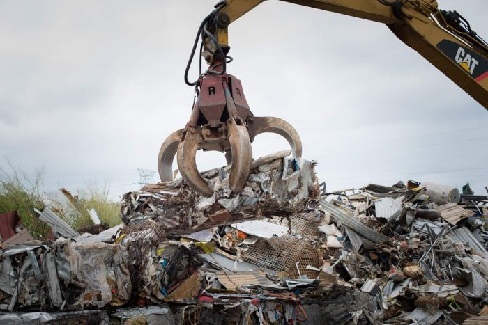 An excavator fitted with a claw loads a bale of recycled steel onto a stack of other bales.