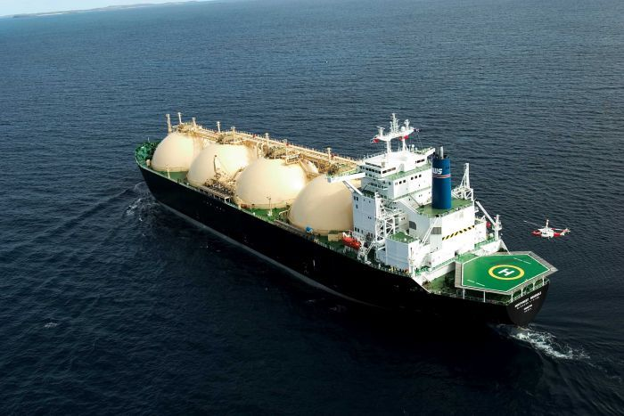 An overhead view of an LNG tanker off the WA coast with a helicopter hovering above its helipad.