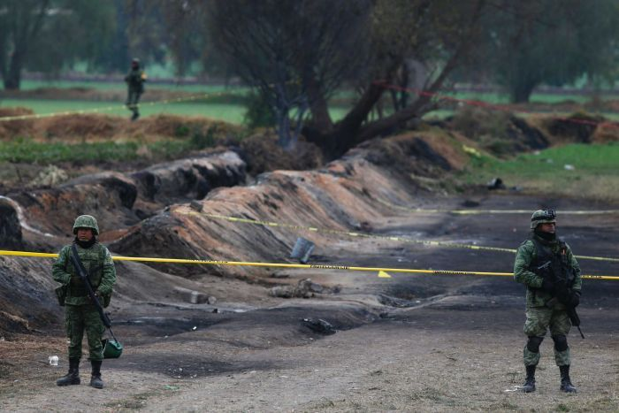 Soldiers guard the site where a gas pipeline exploded two days prior, the earth is scorched.