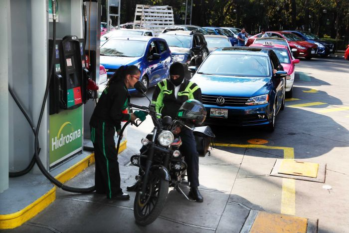 Vehicles stand in line to fill up their fuel tanks at a gas station in Mexico.