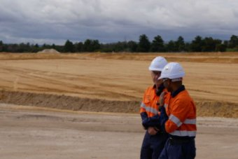 Two construction workers stand on the site of a proposed lithium refinery