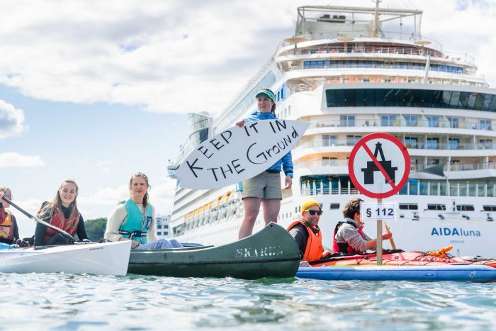 People on canoes on water in front of a cruise ship