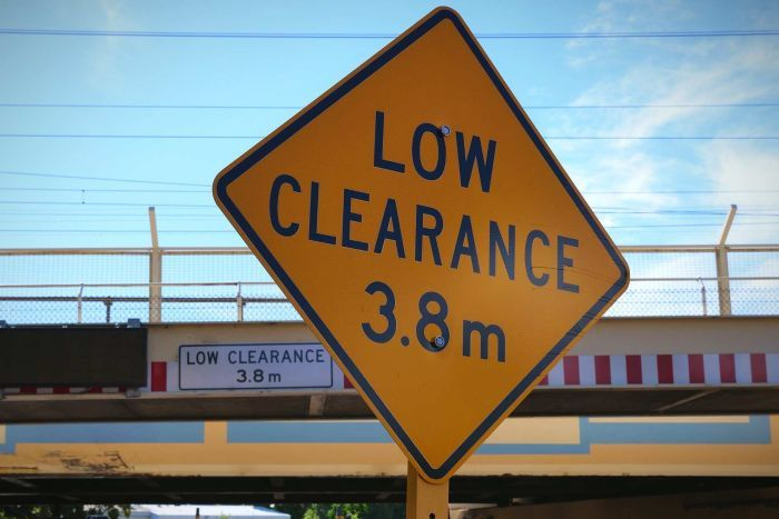 Low clearance bridge sign in foreground with bridge in background