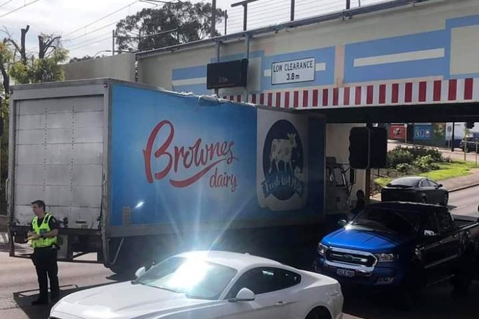 A Brownes Dairy truck is stuck under a bridge, with a police officer standing beside.