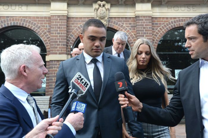 An NRL player and his fiancee are surrounded by microphones as they leave a court.