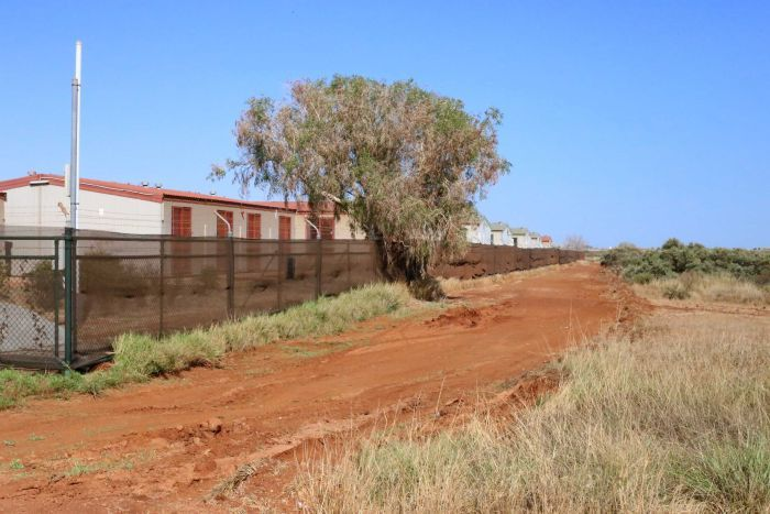 Dongas behind a fence next to a red dirt road and grass.