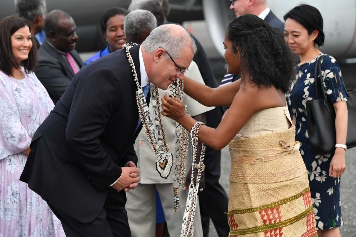 A woman in traditional clothing puts a large necklace on Scott Morrison.