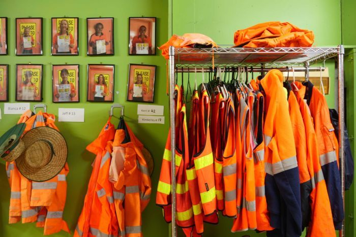 high vis jackets hanging on rail with bright green wall in background.
