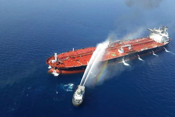 A boat sprays two large streams of water at a stricken oil tanker that is on fire in open water.
