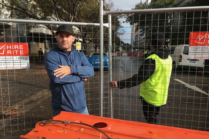 A man wearing a cap stands next to a wire fence.