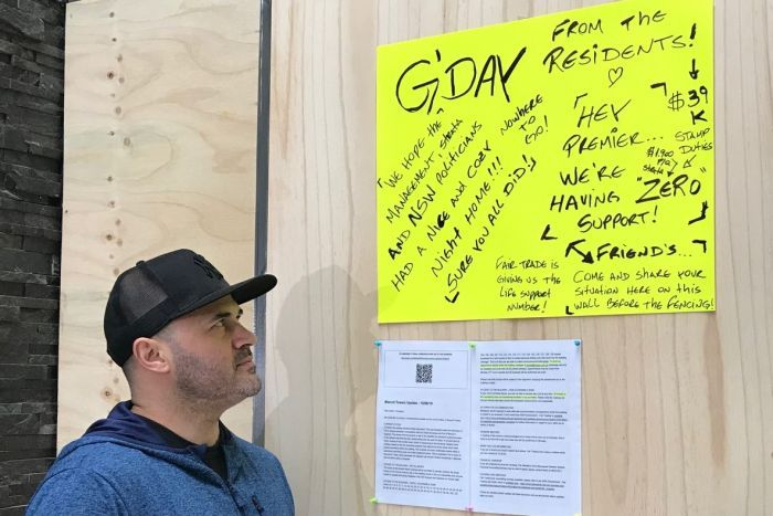 A man in a hat stands in front of a yellow sign stuck on a wall.