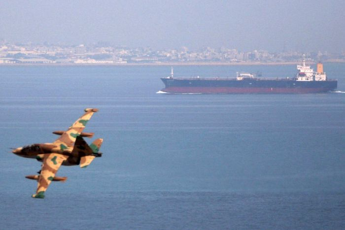 A file photo of an Iranian military fighter plane flying past an oil tanker during naval manoeuvres in the Gulf and Sea of Oman