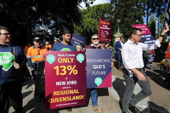A rally of people holding placards with: Fair go for all Queenslanders