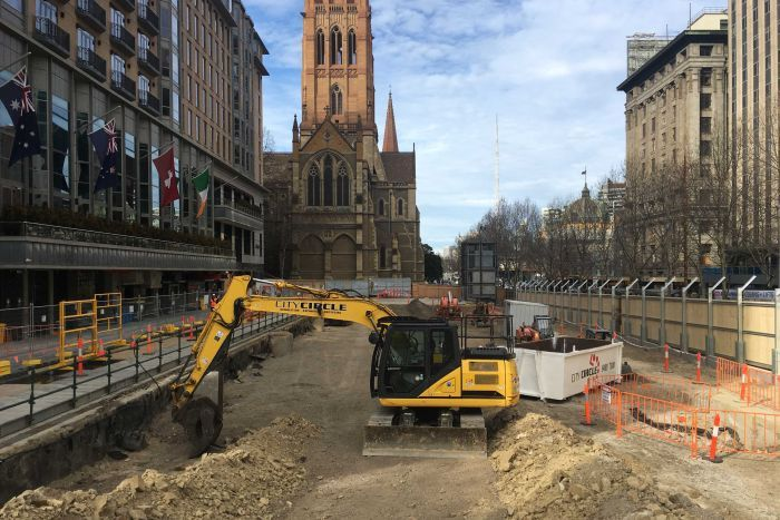 An excavator starts digging in Melbourne's City Square in the shadow of St Paul's Cathedral.