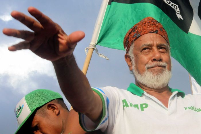 Xanana Gusmao stretches his arm out smiling while a Timorese flag flies behind him
