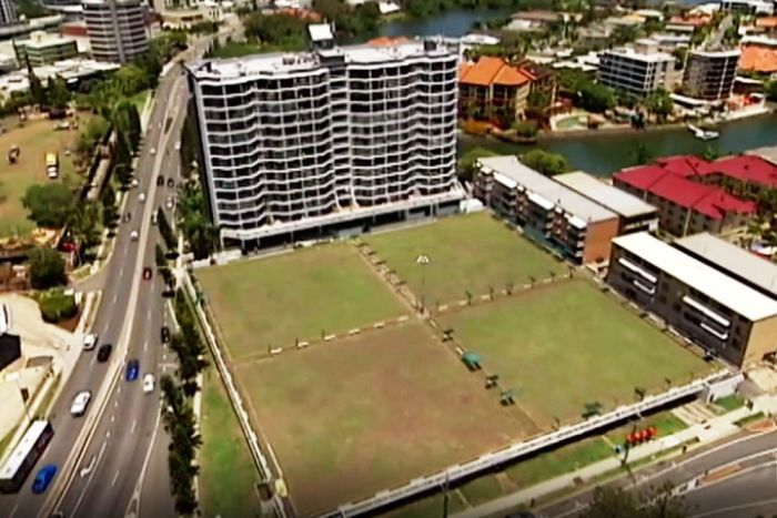 Aerial view of a green surrounded by buildings.