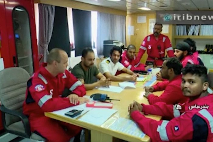 Crew members dressed in red uniforms sit around a table.
