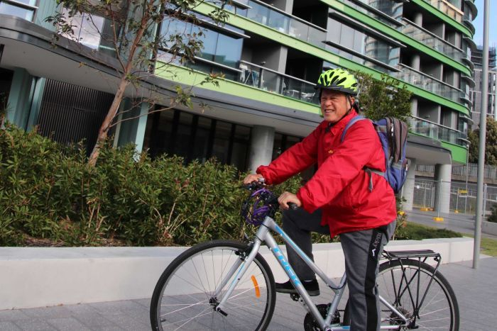 Opal Tower resident Andre on a bike outside the building
