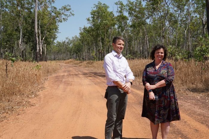 A man and a woman stand in a dirt road surround by scrub