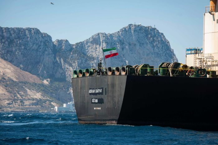 An Iranian flag flies on the deck of a supertanker with mountains seen behind.