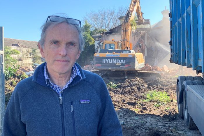 Hawthorn resident Andrew Sutherland looks at the camera as a bulldozer demolishes a house.