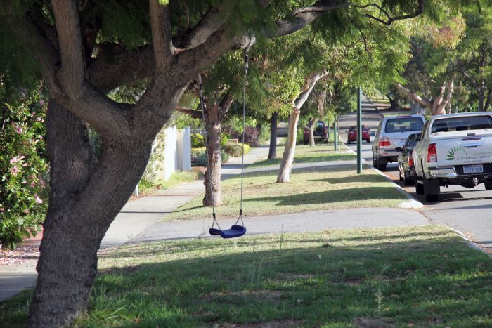 A street in Nedlands with lots of green trees and a child's swing in the foreground.