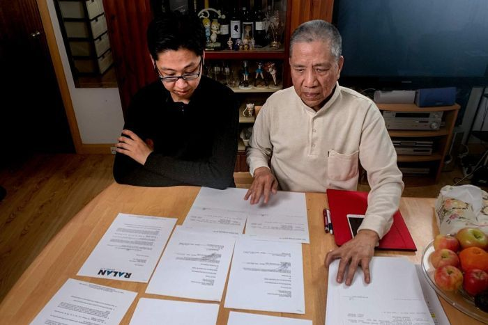 Man with glasses and black shirt next to older man in cream shirt, sitting at dining table with papers scattered in front.
