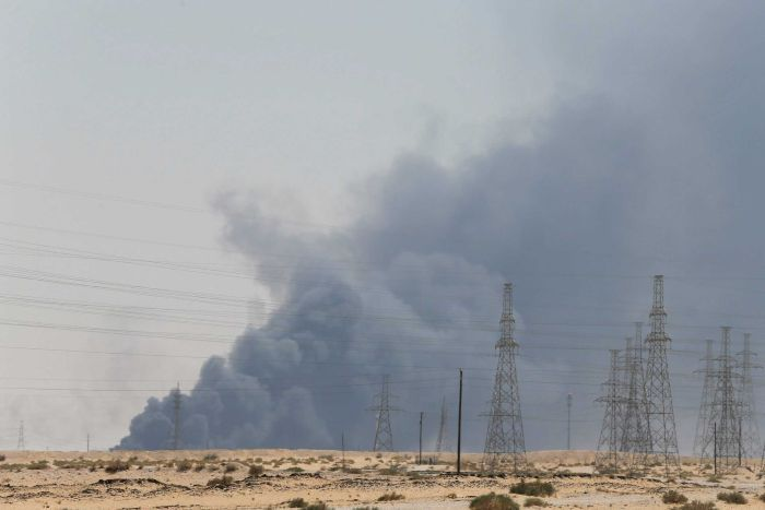 Looking across a Saudi Arabian desert field, you electric cable towers as the horizon is blanketed by dark grey smoke.