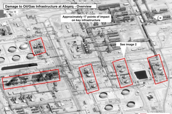 A black and white aerial image shows damage to a Saudi Arabian oil processing facility.