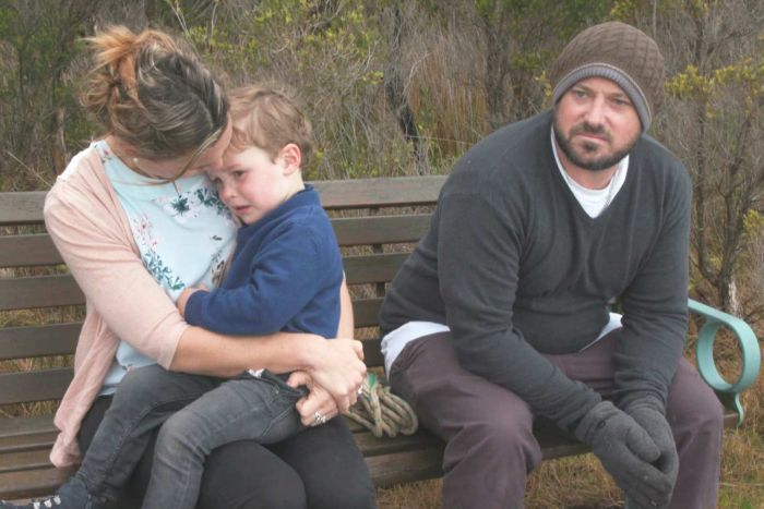 Braden Barnes sits on a bench in the bush. His wife Renee sits on his right with one of their sons sitting on her knee