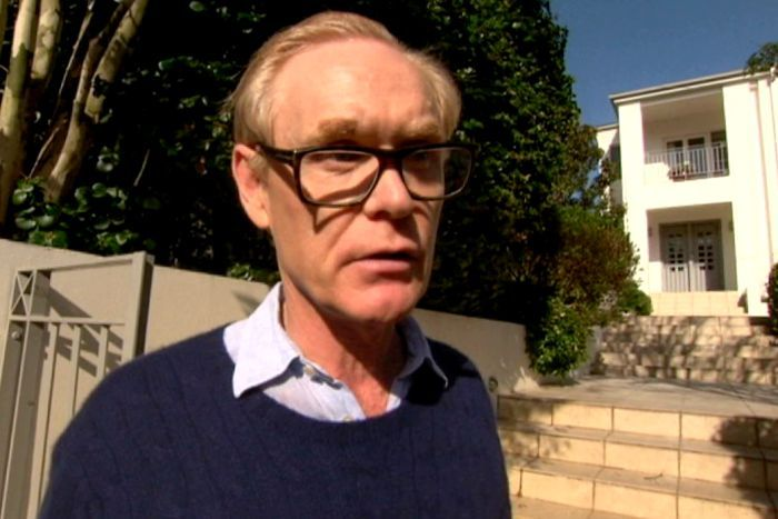 Man with glasses and blue jumper stands outside large home with gate and trees behind him.