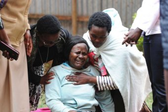 Woman collapses in grief after, with people comforting her