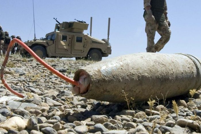 A soldier walks past an Improvised Explosive Device (IED)