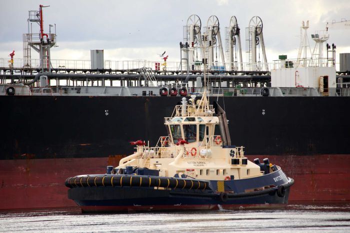 A tug pulls up next to an oil tanker at the Port of Melbourne