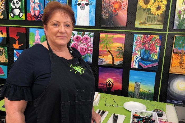 Linda Pearson stands in front of artworks at her business 'Your Creative Palette' at Rochedale.